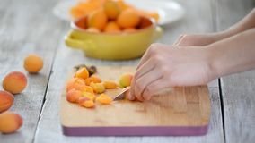Close-up of female hands cutting apricots with a knife on a cutting board. Cooking Vegetarian Food. Close-up of female hands cutting apricots with a knife on a stock video footage