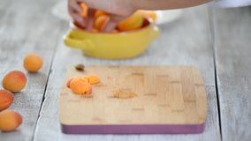 Close-up of female hands cutting apricots with a knife on a cutting board. Cooking Vegetarian Food. Close-up of female hands cutting apricots with a knife on a stock footage