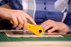 Close-up female hands cutting fabric with patchwork rotating cutter Royalty Free Stock Image