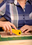Close-up female hands cutting fabric with patchwork rotating cutter Royalty Free Stock Photography