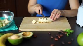 Woman Slicing Banana on a Board for Smoothie. Close up of Female Hands Cutting Fresh Banana on a Board for Preparing Smoothie in Slow Motion. Healthy Lifestyle stock video footage