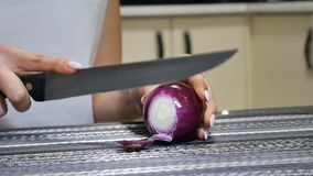 Close up of female hands cutting red onion while cooking vegetables salad in the kitchen. Close up of female hands cutting red onion while cooking vegetables stock video