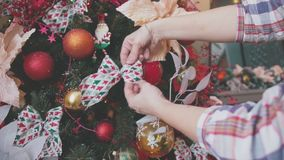 Close-up of female hands decorate the Christmas tree. stock footage