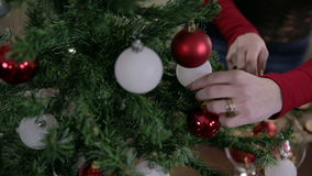 Close up on female hands decorating Christmas tree stock video footage