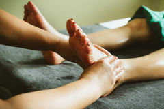 Close-up of female hands doing foot massage. Royalty Free Stock Images