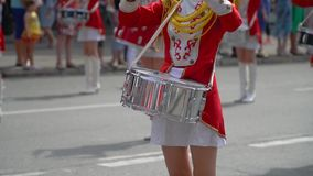 Close-up of female hands drummers are knocking in the drum of their sticks. Slow motion. Young girls drummer in red at the parade. Street performance on the stock footage