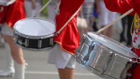 Close-up of female hands drummers are knocking in the drum of their sticks. Street performance of festive march of. Young girls drummer in red at the parade stock video footage