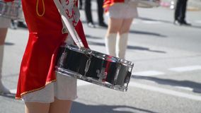 Close-up of female hands drummers are knocking in the drum of their sticks. Street performance on the occasion of the. Young girls drummer in red at the parade stock video