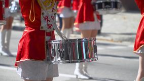 Close-up of female hands drummers are knocking in the drum of their sticks. Young drummers line up and beat the melody. Young girls drummer in red at the parade stock video footage