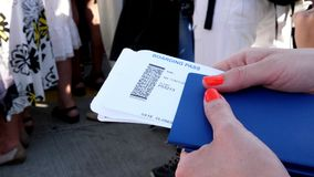 Close-up, female hands holding Airline boarding pass tickets, Boarding pass and passport at airport.  stock footage