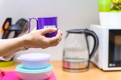 Hands hold plastic cup with smiling face. Close up female hands holding bright violet tea mug with a funny face on it Royalty Free Stock Image