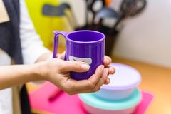 Hands hold plastic cup with smiling face. Close up female hands holding bright violet tea mug with a funny face on it Stock Images