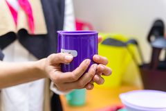 Hands hold plastic cup with smiling face. Close up female hands holding bright violet tea mug with a funny face on it Stock Photo