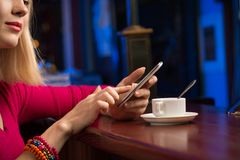 Close-up of female hands holding a cell phone. Sitting at the bar, next to a cup of coffee royalty free stock images