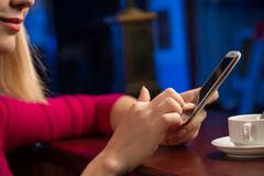 Close-up of female hands holding a cell phone. Sitting at the bar, next to a cup of coffee royalty free stock photo