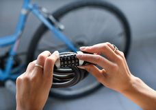 Combination bike lock in female hands. Close up of female hands holding combination bike lock with bicycle blurred in background Royalty Free Stock Photography