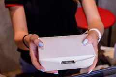 Close up female hands holding and giving take out food in white paper box through the window of issuing orders. Selective focus. S royalty free stock images
