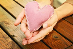 Close up on female hands holding a heart. Love, handmade, valentine concept Stock Image
