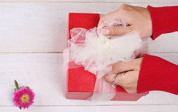 Close up on female hands holding red present with white Ribbon . Gift box packaging. Birthday, New year, Valentine's Day, 8 march, Royalty Free Stock Photo