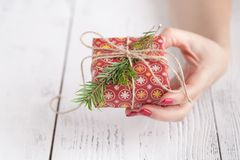 Close up of female hands holding a small christmas gift wrapped with twine. Small gift in the hands of a woman indoor. Shallow dep Royalty Free Stock Photography