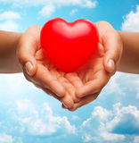 Close up of female hands holding small red heart Royalty Free Stock Photo
