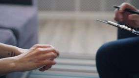 Close up of female hands holding tissue and psychologist writing notes in office. Close up shot of female patient`s hands moving holding tissue and psychologist stock video footage