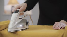 Close-up of female hands ironing yellow sweater. Young muslim housewife doing housework. Eastern culture, modern society