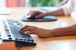 Close up of female hands with keyboard and mouse Royalty Free Stock Image