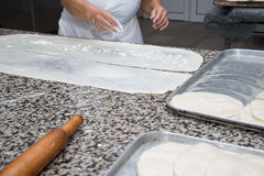 Close up of female hands kneading dough and making banitsa Stock Photos