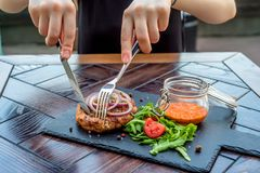 Woman`s hands cut beefsteak on board in restaurant royalty free stock images