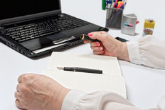 Close-up of female hands with laptop, smartphone and notebook Stock Photography