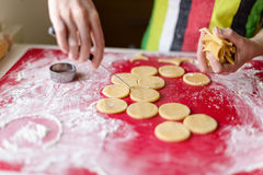 Close up of female hands making cookies from fresh dough at home Royalty Free Stock Photos