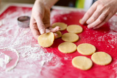Close up of female hands making cookies from fresh dough at home Stock Photo