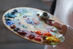 Close-up of female hands mixing paints on a palette with a spatula creating an oil painting. Soft focus stock images