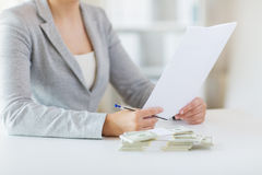Close up of female hands with money and tax report Royalty Free Stock Image