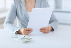 Close up of female hands with money and tax report Royalty Free Stock Images