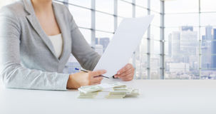 Close up of female hands with money and tax report Royalty Free Stock Photo
