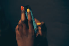 Close-up of female hands with nail art using smartphone. Close-up of female hands with nail art holding and using smartphone, dark blurred background Stock Photo