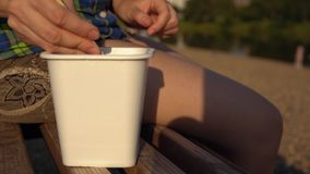 Young woman eats instant noodles from box on deck chair. Close up of female hands picking up piece of chicken with wooden chopsticks. Young woman in checkered stock video