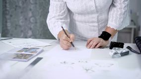 Close up of female hands with pin cushion and pencil drawing outline. Image of body of a woman in white blouse and skirt