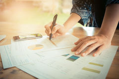 Close-up of female hands pointing at turnover graph while discus Royalty Free Stock Images