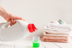 Close up of female hands pouring liquid laundry detergent into cap on white rustic table with towels on background in Stock Image