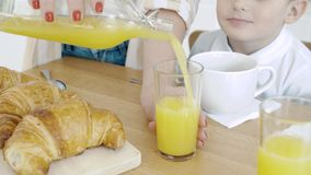 Close-up of female hands pouring orange juice into a glass. Breakfast.