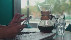 Close-up of female hands print sms on your mobile phone in a cafe. Freshly brewed coffee and a newspaper on the table. Coffee maker Chemeks on the table. A woman stock video footage