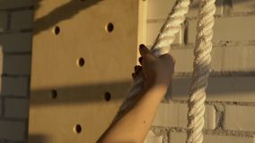 Close-up of female hands pull thick edging during workout on crossfit. Against background of wall made of white brick female athlete performs exercises for stock video
