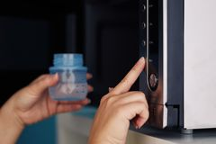 Female hands putting a baby bottle with water into a microwave. Close up of female hands putting a baby bottle with water into a microwave Royalty Free Stock Image