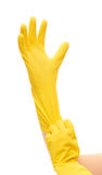 Close up of female hands putting on yellow protective rubber gloves Royalty Free Stock Photo