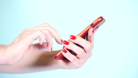 Close-up, female hands with red manicure use a smartphone on a colored background. 4k, slow-motion shooting stock footage