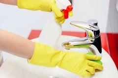 Close up of female hands with rubber gloves cleaning tap. Stock Photo
