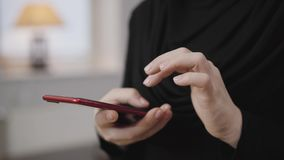 Close-up of female hands scrolling on smartphone. Young Muslim woman in black clothes using mobile phone. Modern society
